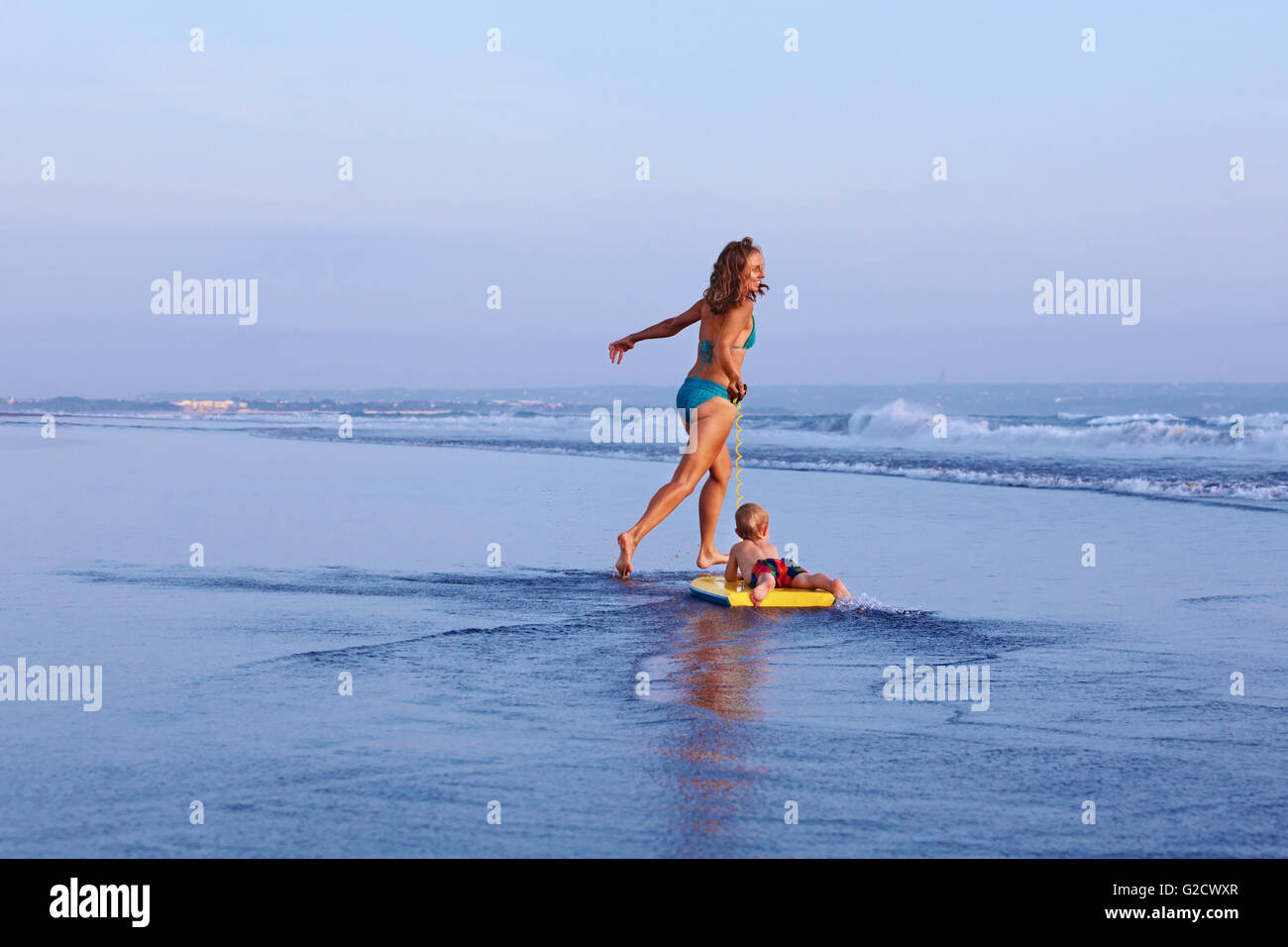 Happy family having fun - mother with baby son on surfing board run by water pool along sea surf of sunset beach. - Stock Image