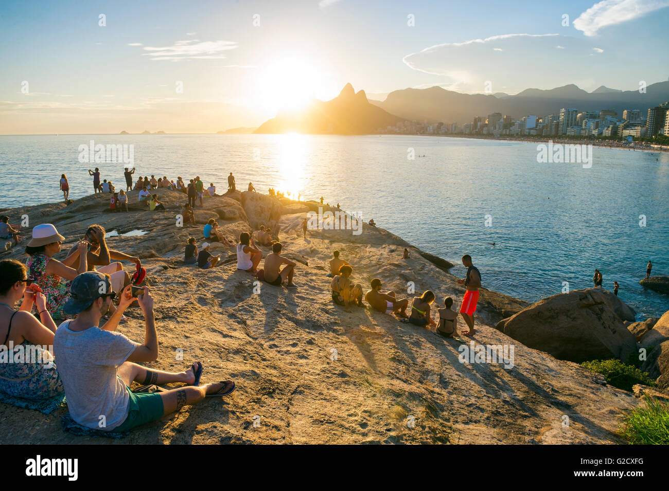 RIO DE JANEIRO - FEBRUARY 26, 2016: Crowds of people gather to watch the sunset on the rocks at Arpoador. - Stock Image