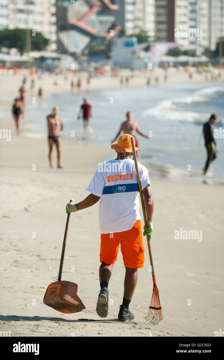 RIO DE JANEIRO - APRIL 3, 2016: Worker from the municipal COMLURB maintenance company cleans the sand on Copacabana - Stock Image