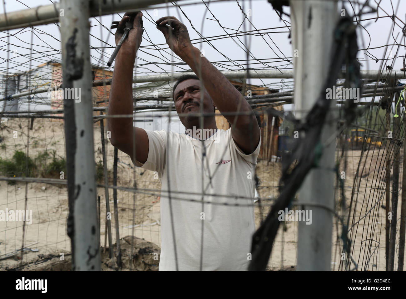 Idris from Eritrea rebuilds his home burned in clashes in the migrant camp dubbed the 'Jungle' on the outskirts Stock Photo