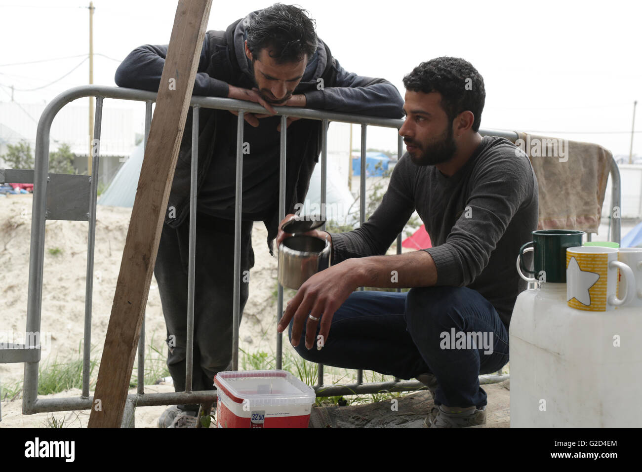 Walid and Ibrahim talk outside their home in the migrant camp dubbed the 'Jungle' on the outskirts of Calais, France, Stock Photo