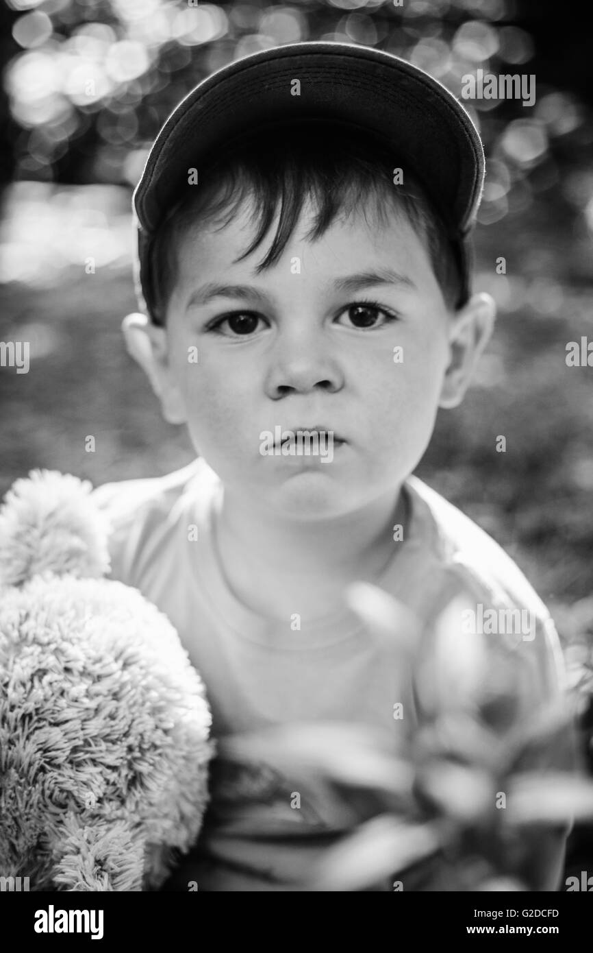 Portrait of Young Boy Holding Stuffed Animal - Stock Image