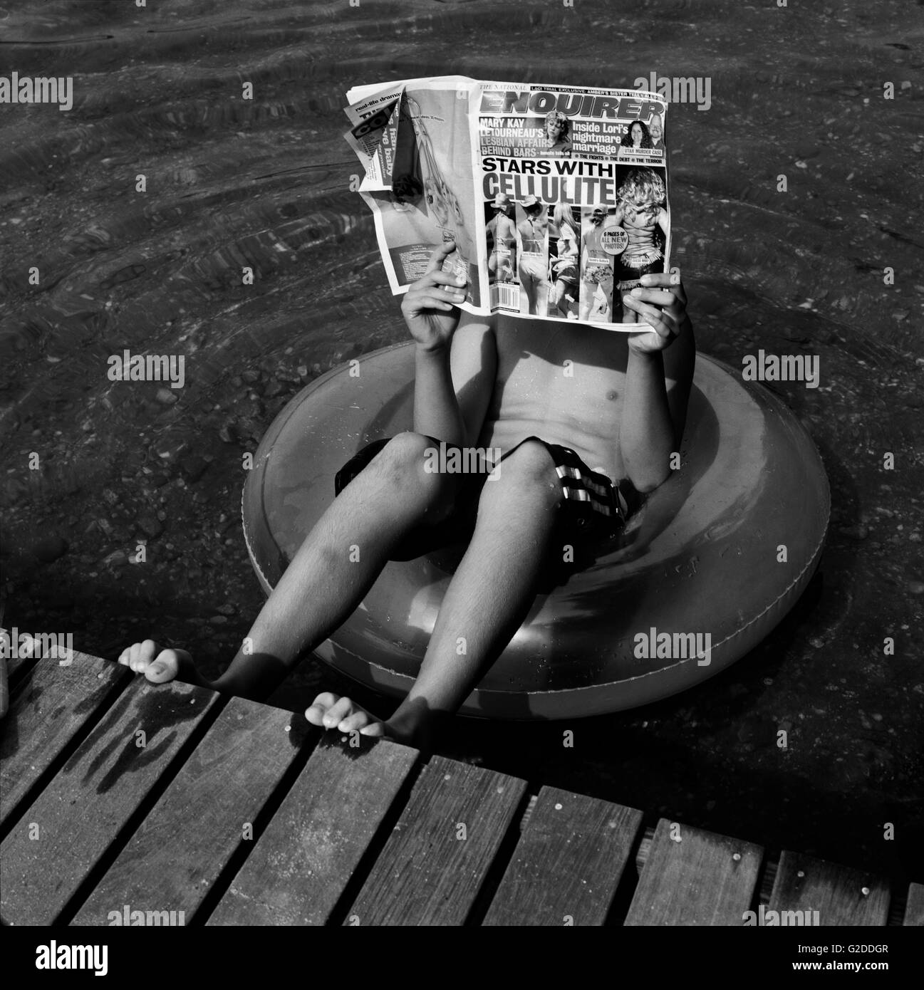 Boy Reading Newspaper While Sitting in Inflatable Tube - Stock Image