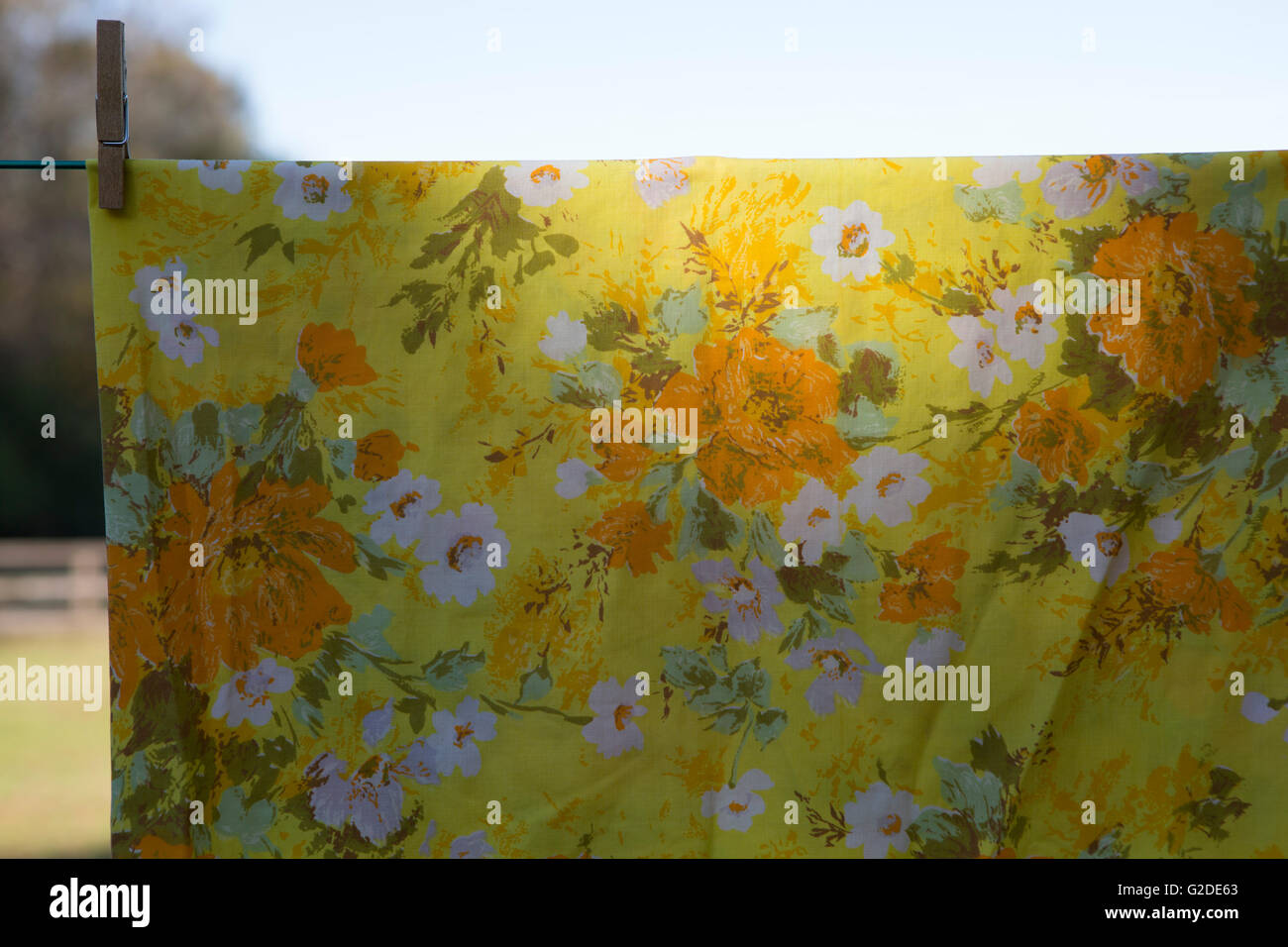 Yellow Floral Sheet Hanging on Clothesline - Stock Image