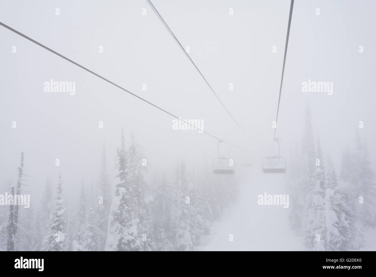 Foggy Snowy Trees and Ski Chairlift in Distance Stock Photo