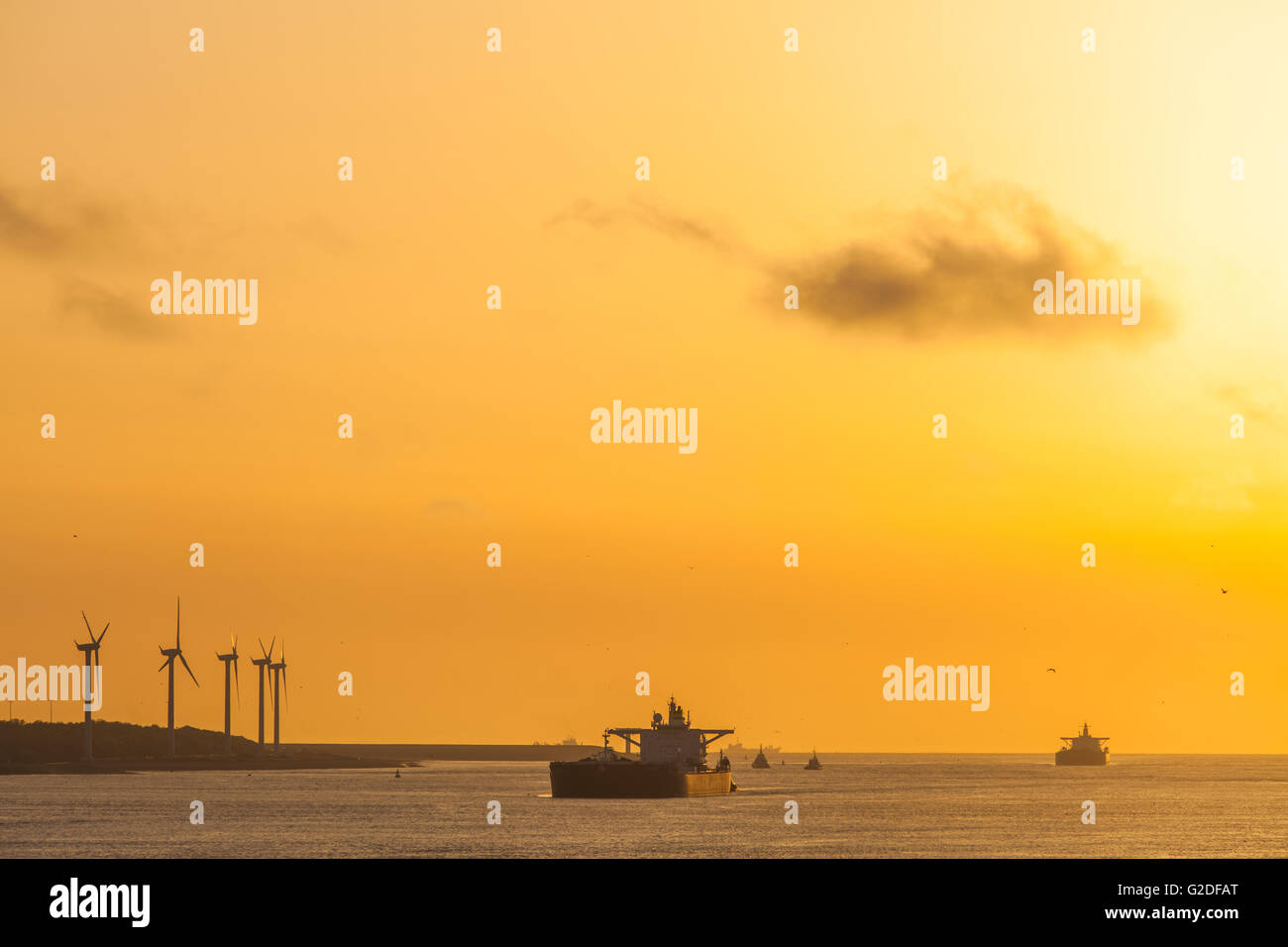 Two loaded crude oil tankers entering Port of Rotterdam Netherlands contrasting with windpark turbines green power Stock Photo