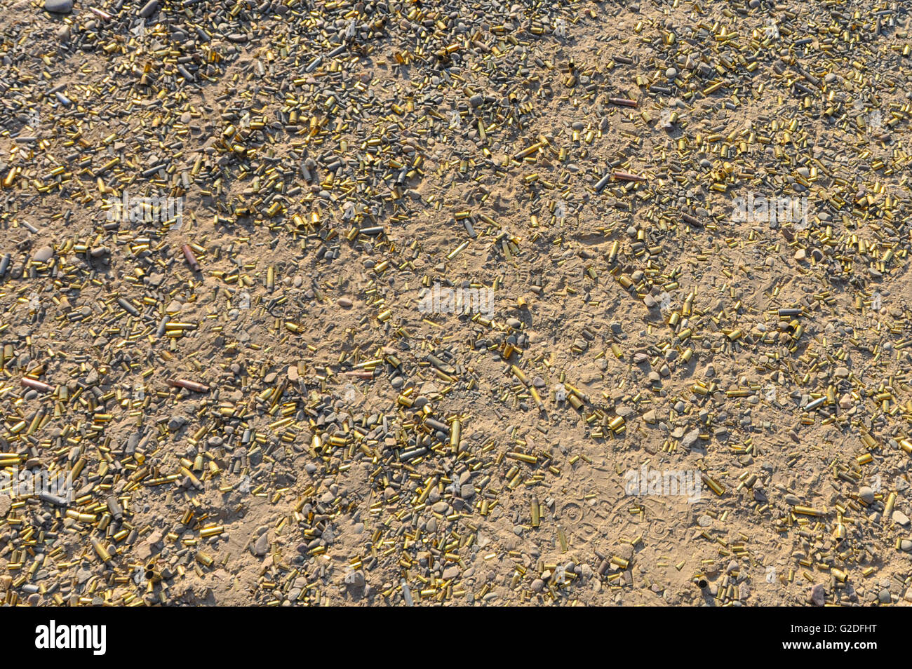 a shot of a ground riddled with spent shell casings from the discharging of guns at a gun range - Stock Image