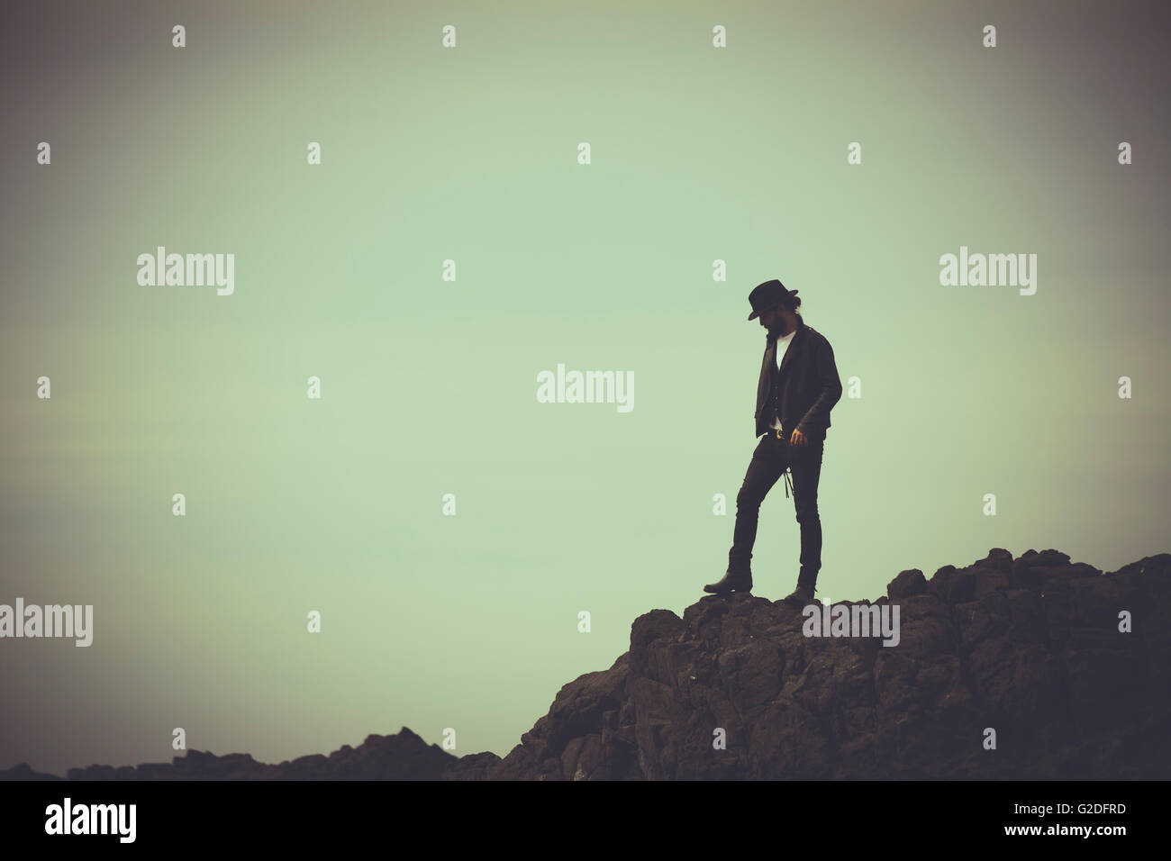 Contemplative Young Adult Man Standing on Cliff Rocks - Stock Image