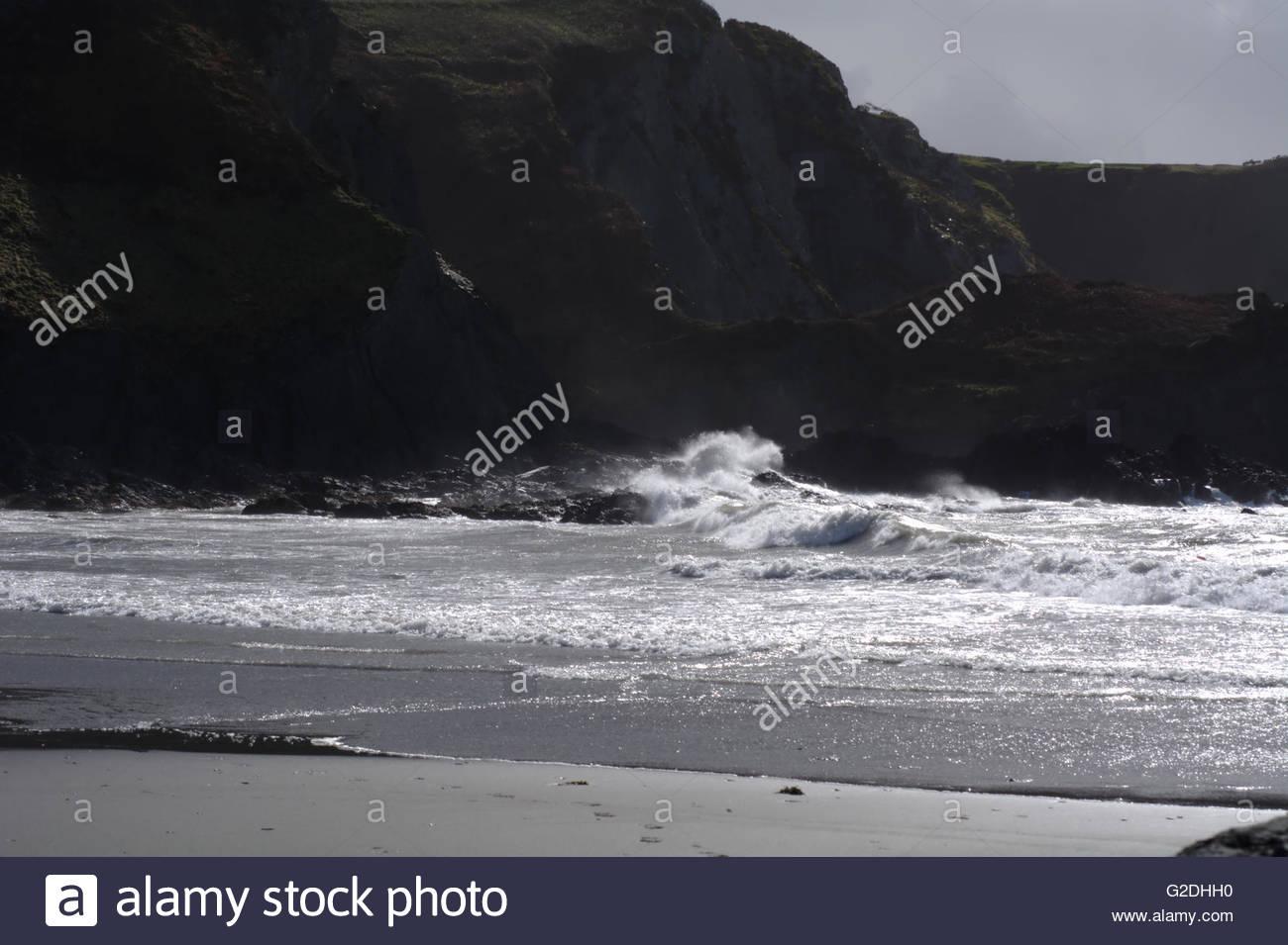 Storm at sea smashing over shore rocks - Stock Image
