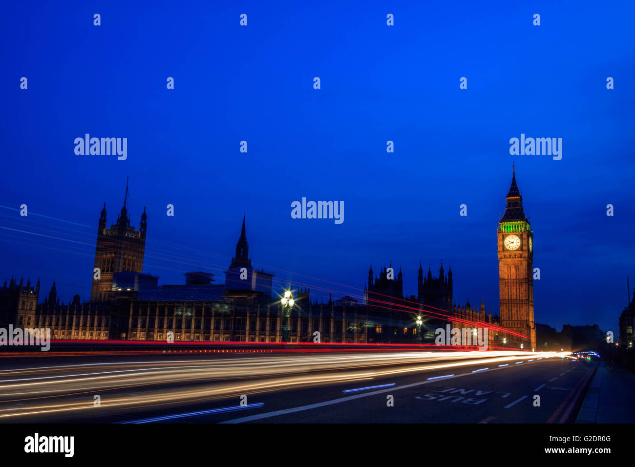 Palace of Westminster in London, and the Big Ben at night with vehicle leaving a trail along the road, with a clear - Stock Image