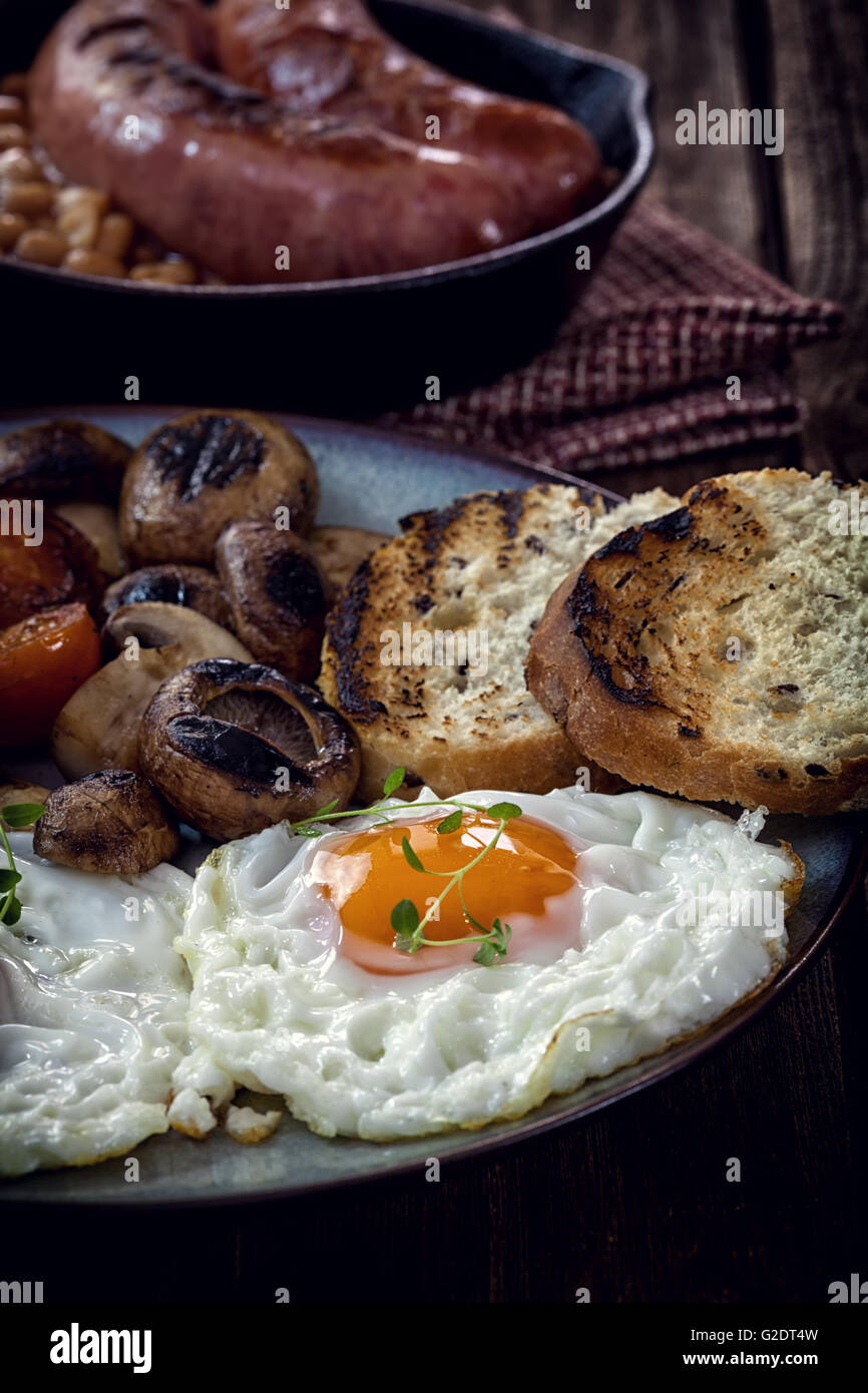 English breakfast with eggs, tomatoes, mushrooms, bacon, beans - Stock Image
