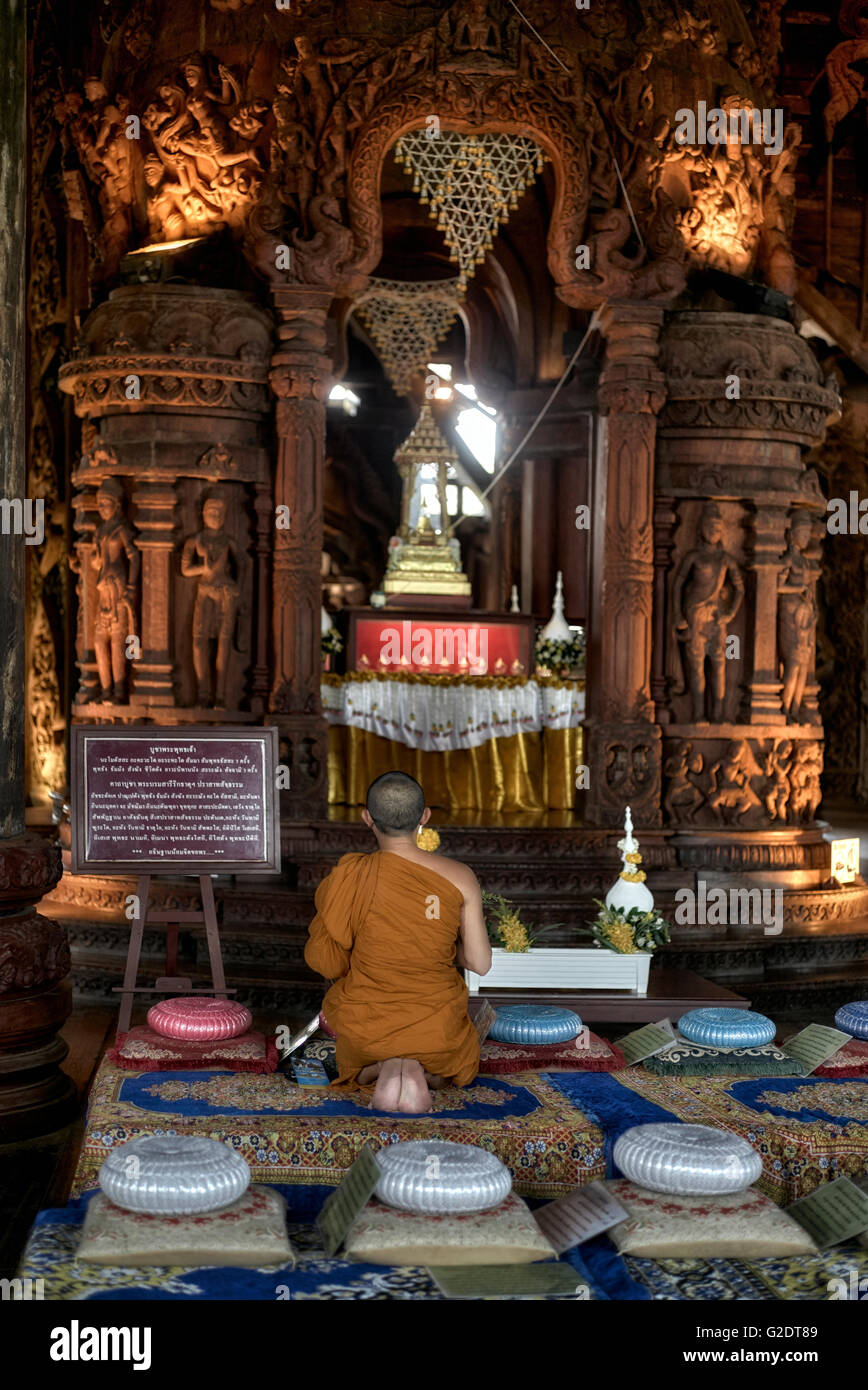 Solitary monk praying at the Sanctuary of truth Buddhist Hindu temple. Pattaya Thailand S. E. Asia - Stock Image