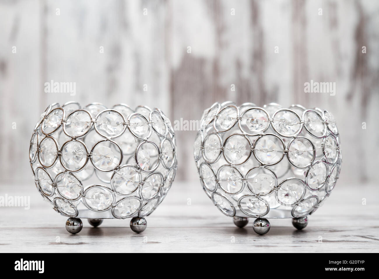 Candle holders with crystals on white wooden background - Stock Image