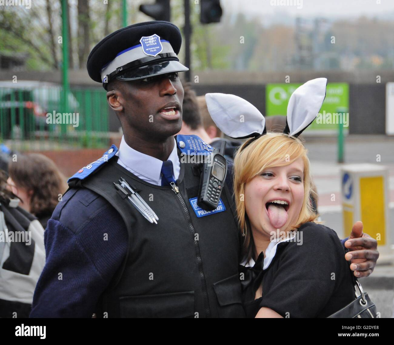 A young girl posses with a traffic warden in Kentish Town, London, after having enjoyed a Sunday afternoon at the - Stock Image