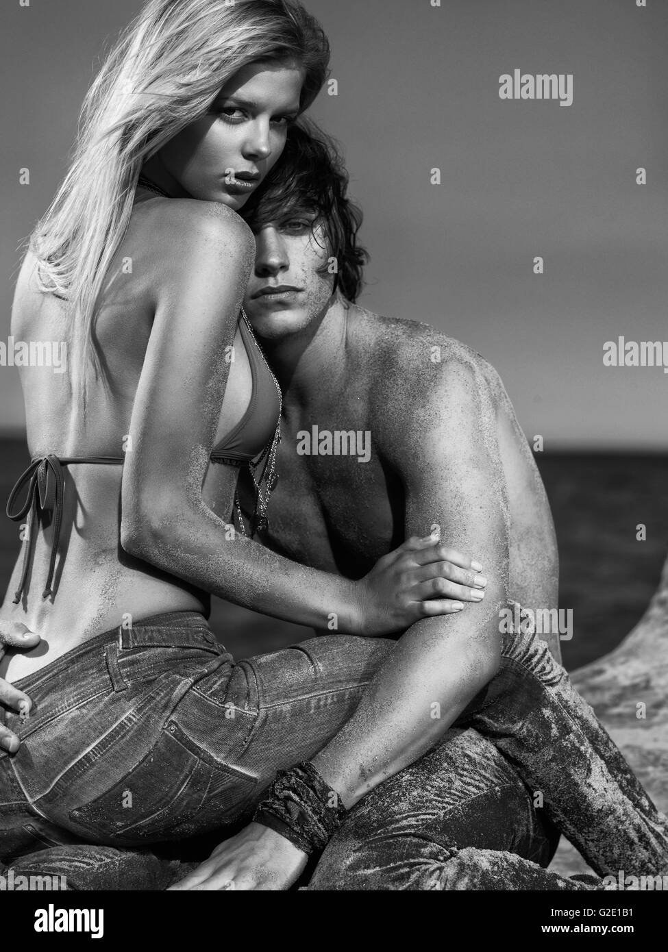 Lovers sitting on the beach, the man resting his head on the woman's chest, Toronto, Ontario Province, Canada - Stock Image