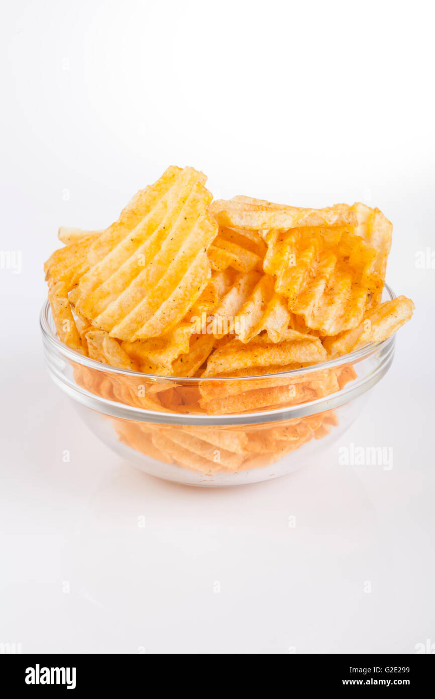 Glass bowl full with golden spicy potatoe chips on white background - Stock Image