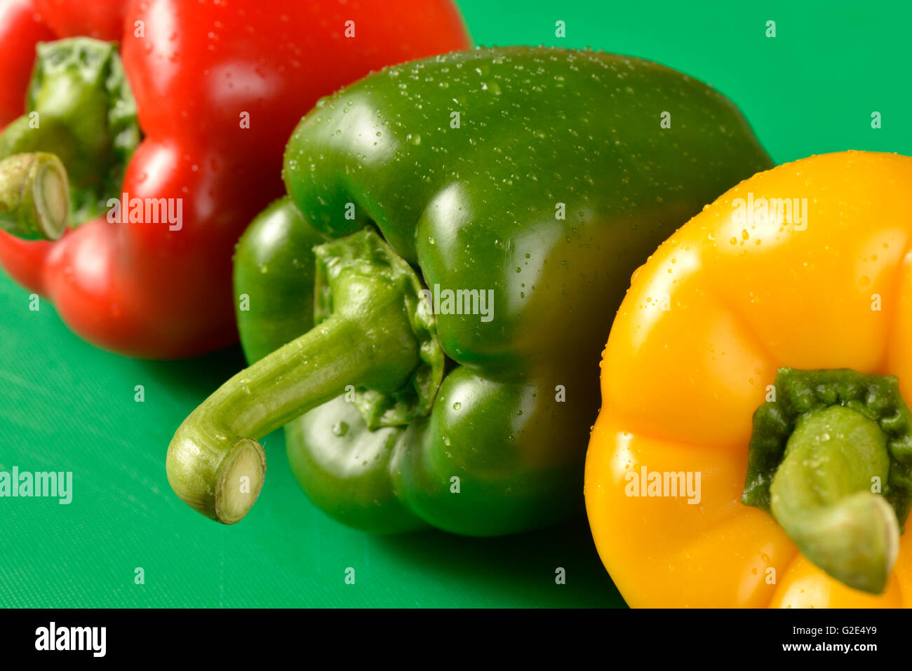Red, green and yellow bell peppers on green chopping board - the correct colour board for food hygiene requirements - Stock Image