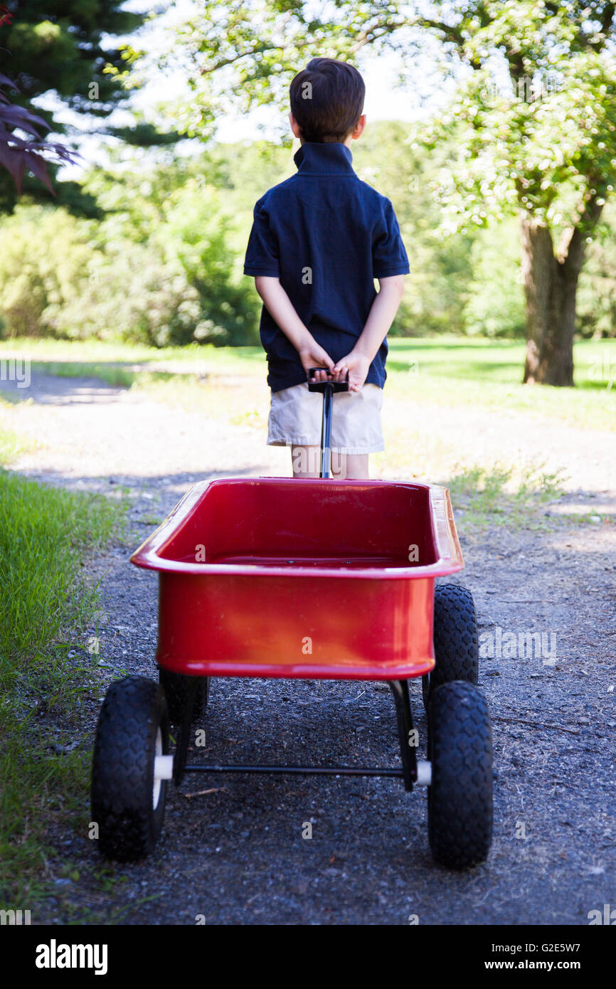 Young Boy Pulling Red Wagon, Rear View - Stock Image