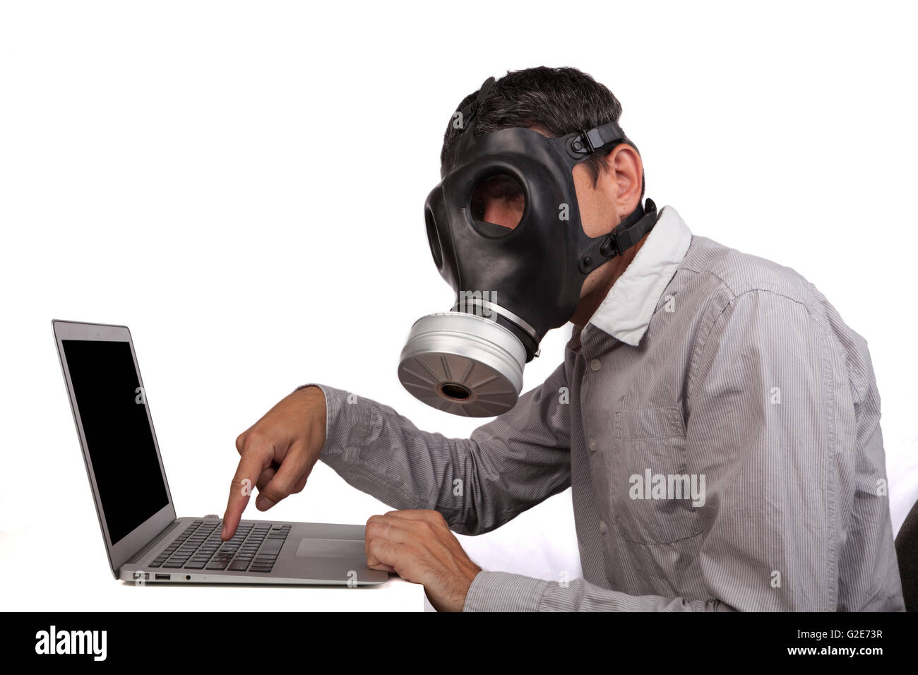 Man with gas mask working with silver laptop isolated on white background - Stock Image