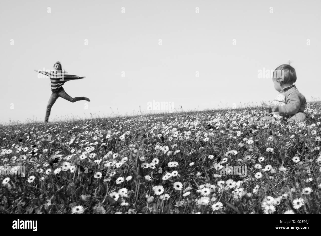 Woman Jumping in Field of Wildflowers with Baby Sitting in Foreground - Stock Image