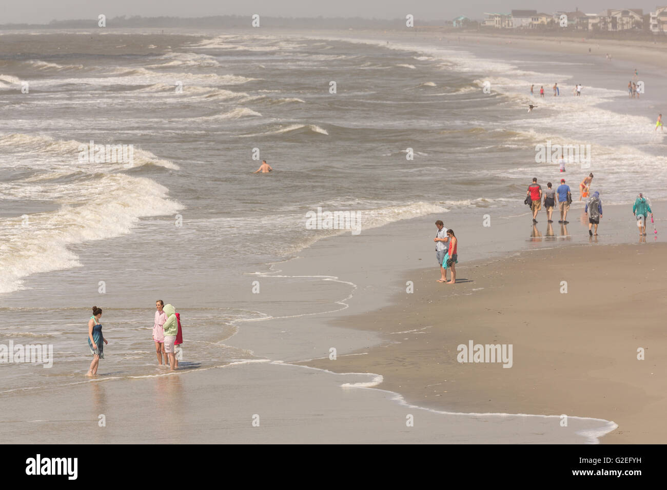 Folly Beach, South Carolina, USA. 29th May, 2016. Vacationers stand watching the surf as Tropical Storm Bonnie, - Stock Image