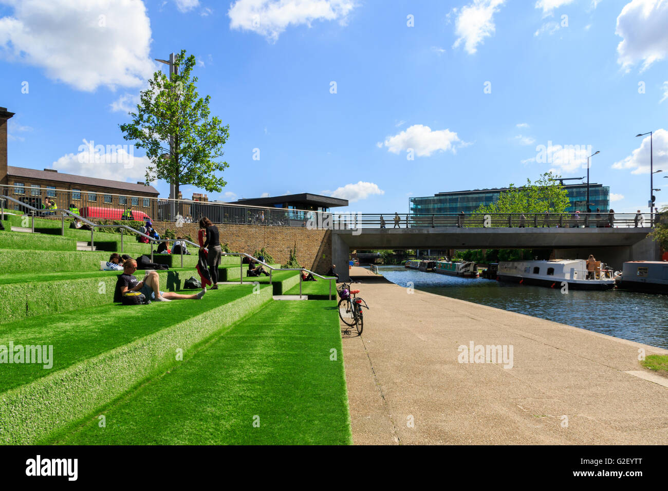 London, UK - May 23, 2017 - People relax and enjoy sunshine on the terrace at Granary Square, King's Cross - Stock Image