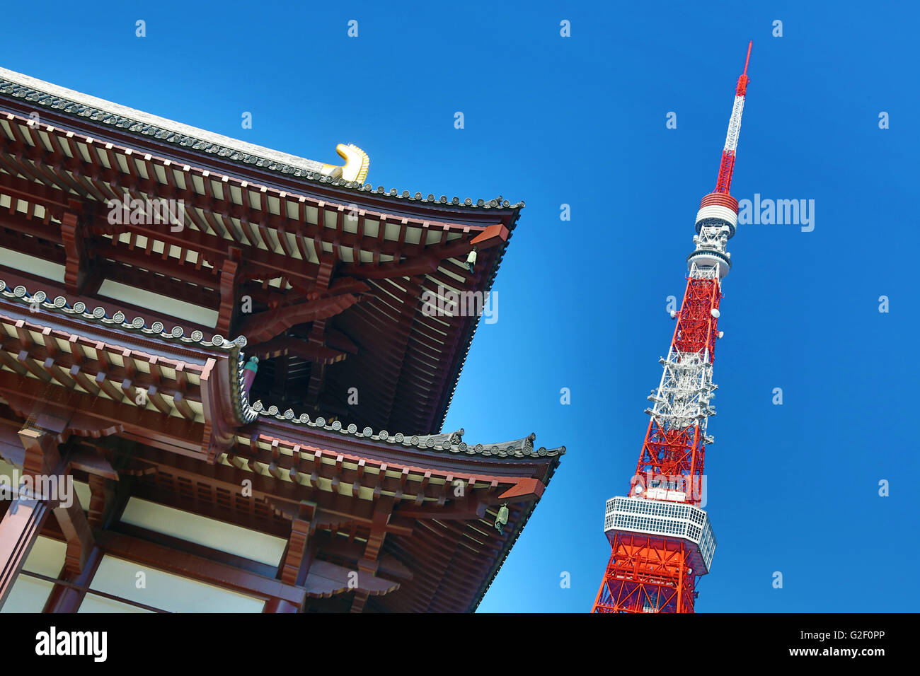 Roof of the Daiden (Hondo) the main hall of Zojoji Temple and the Tokyo Tower in Tokyo, Japan - Stock Image