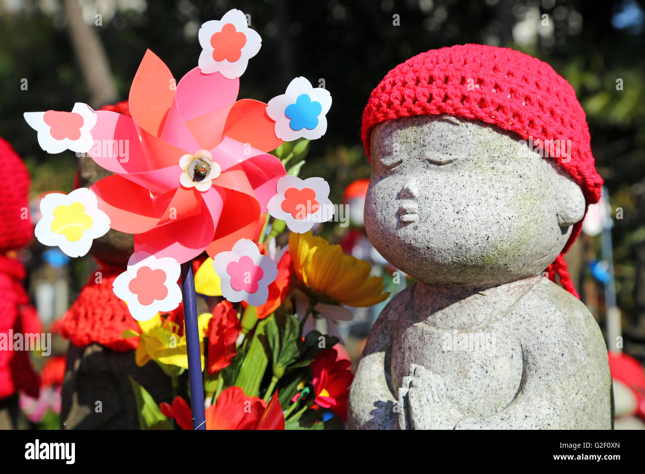 Jizo statues and pinwheel windmill toys in the Zojoji Temple cemetery garden in Tokyo, Japan - Stock Image