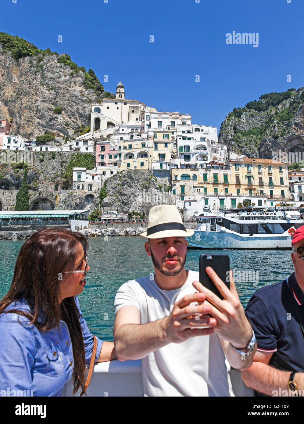 An man with an attractive young woman taking a selfie on a boat trip around the Amalfi Coast Italy Europe - Stock Image