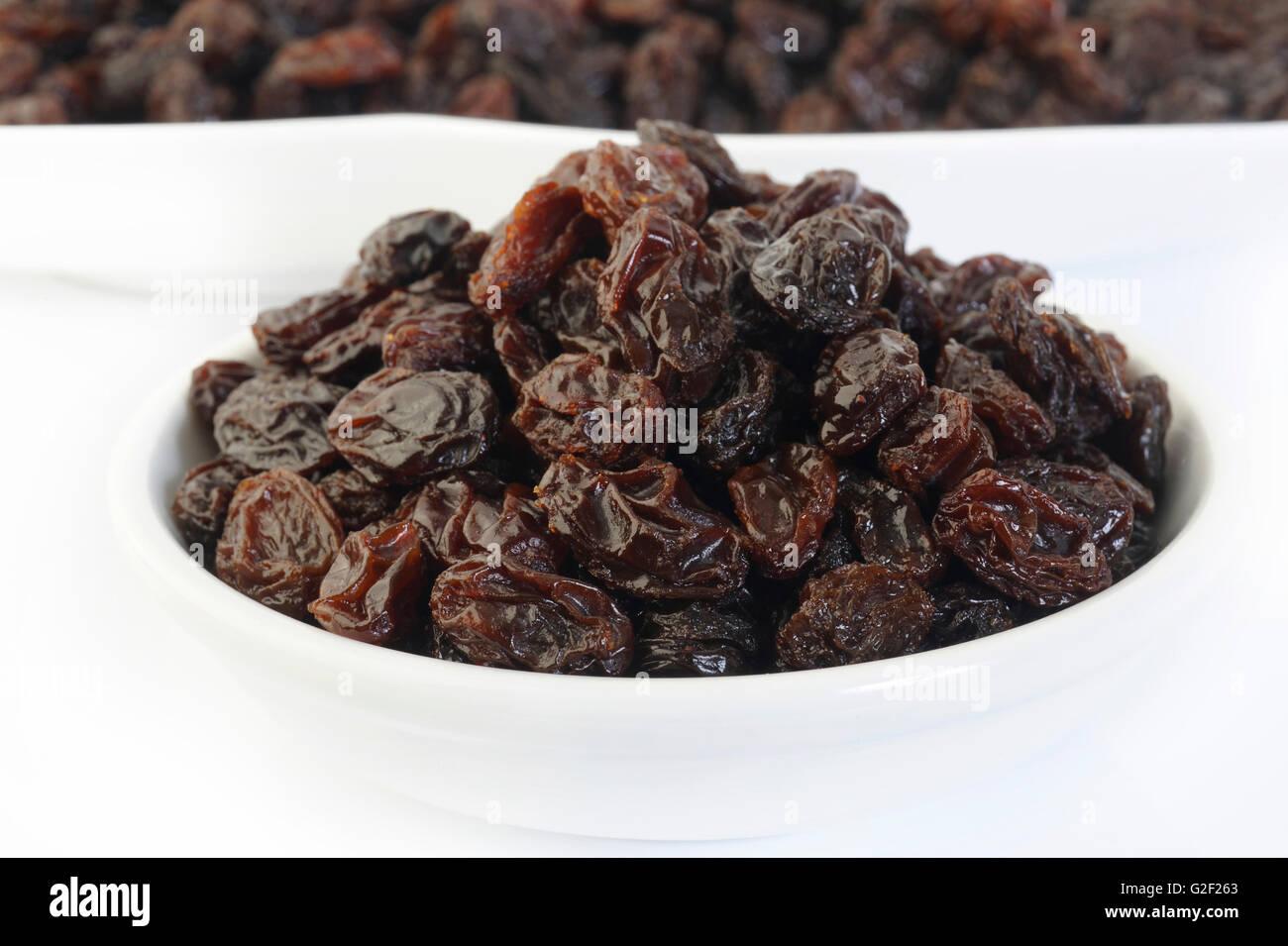 Bowl of raisin on white background - Stock Image