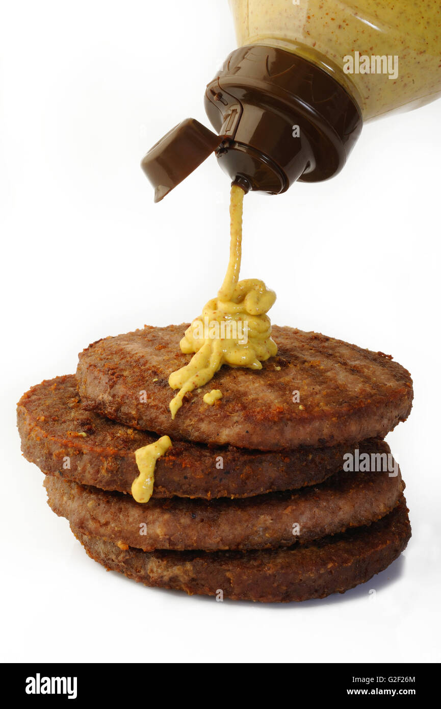 mustard sauce falling from bottle on burger cutlet beef minced meat - Stock Image