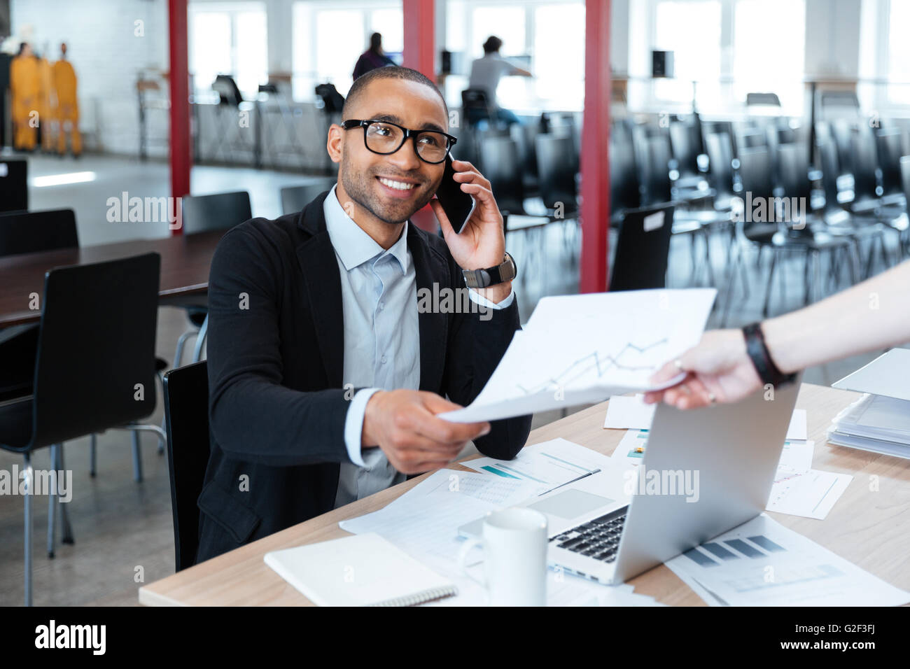 Smiling bisnessman giving papers to someone in office - Stock Image