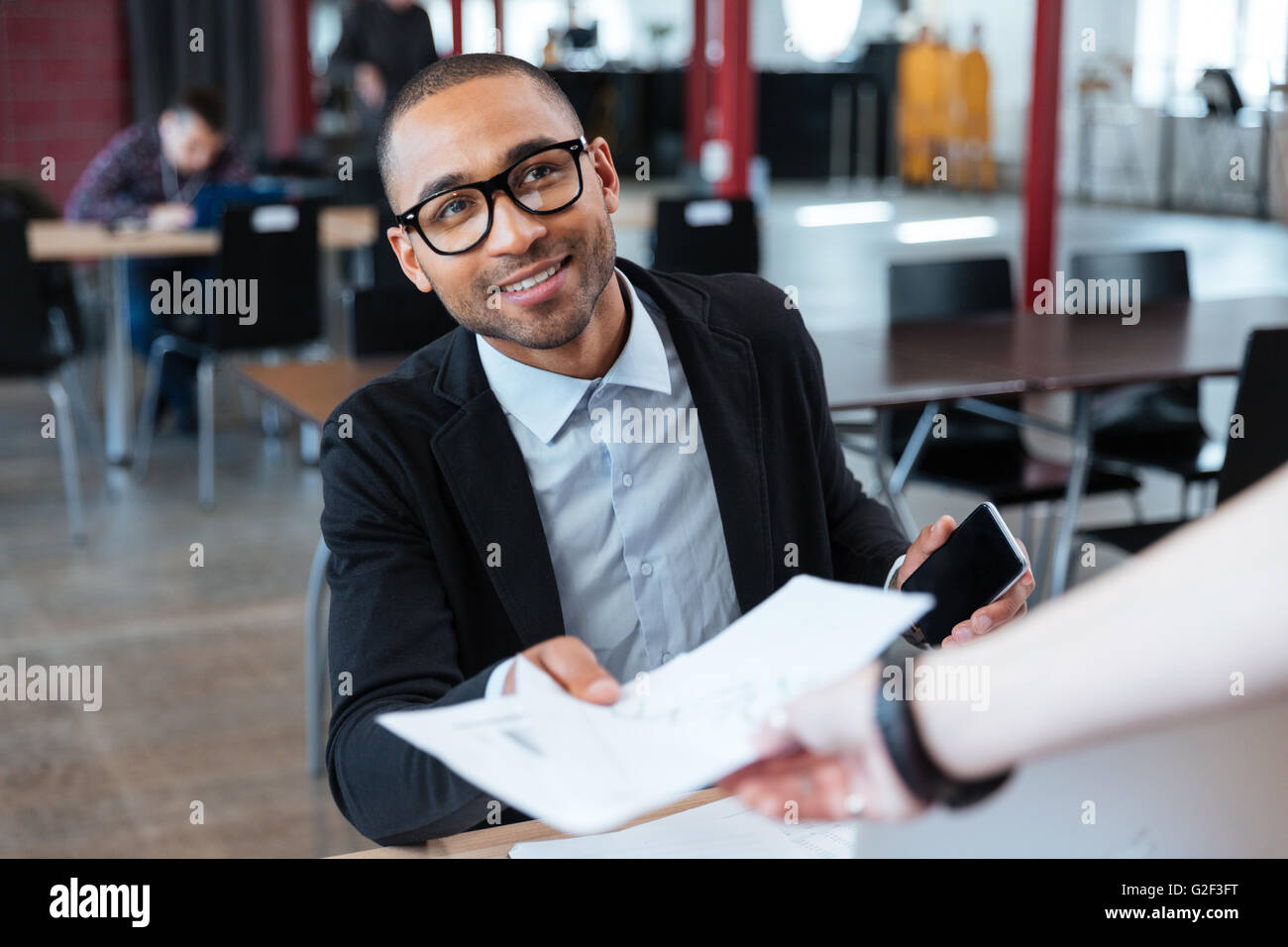 Young businessman giving papers to someone in the office - Stock Image