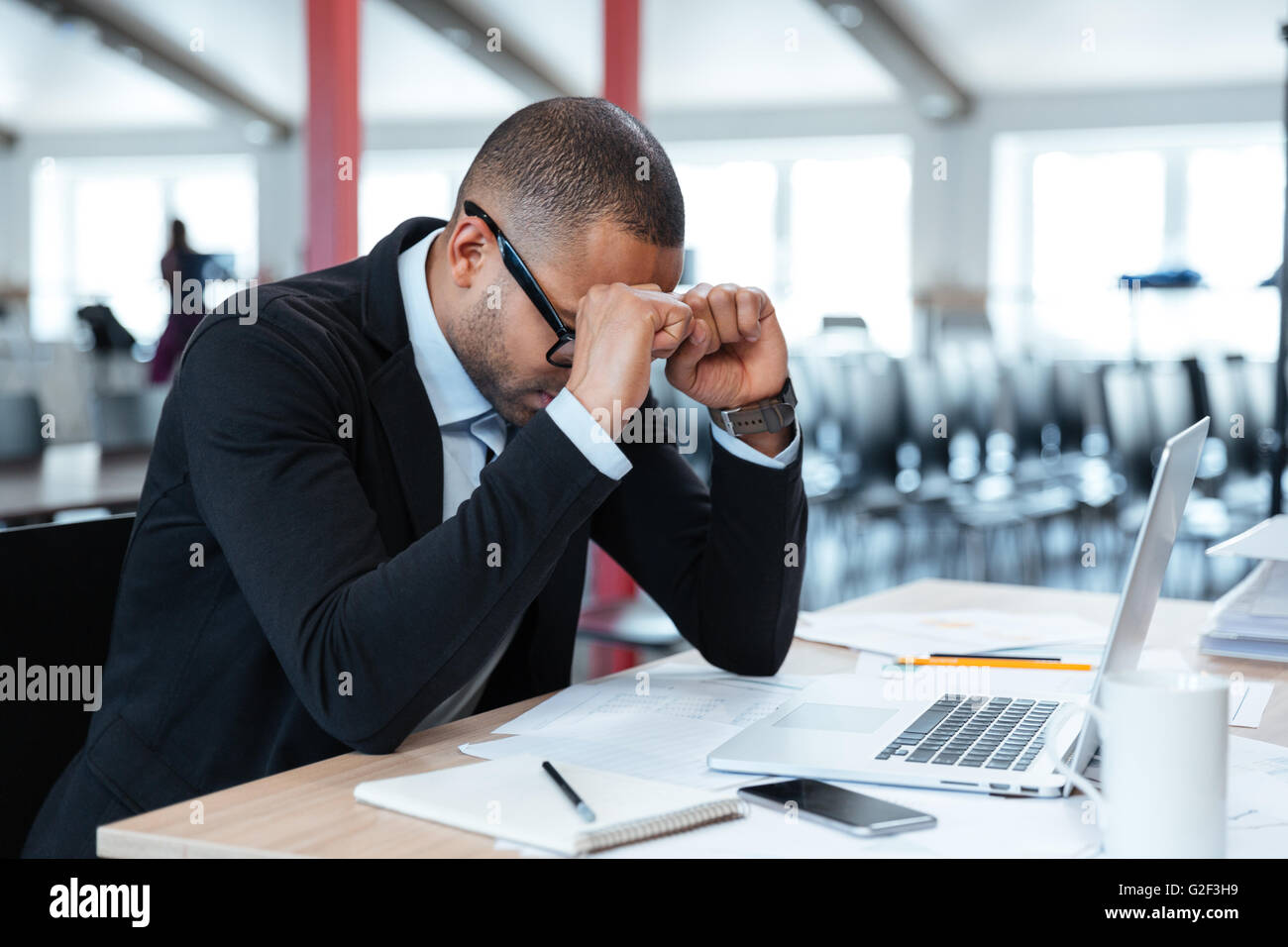 Overworked, depressed and exhausted businessman at his desk with a pile of work - Stock Image