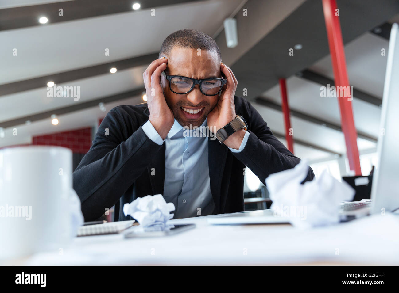Exhausted businessman at work in the office - Stock Image