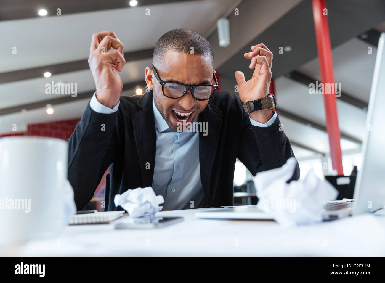 Shouting tired businessman at his desk at the office - Stock Image