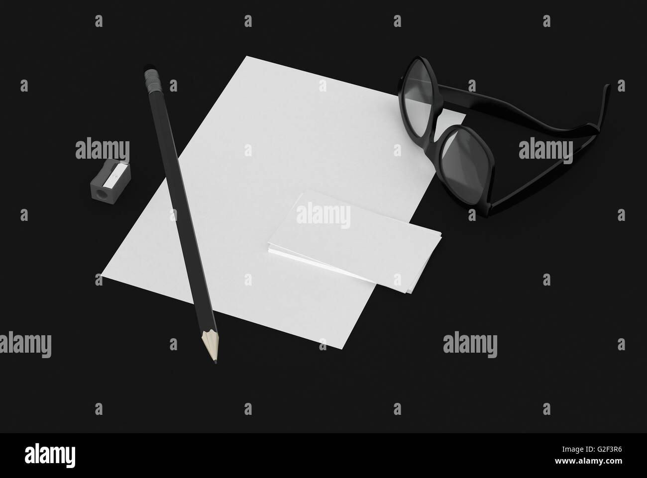 High Angle Still Life of Office Supplies on Black Desk - Black White Page and Business Card with Pencil, Sharpener Stock Photo