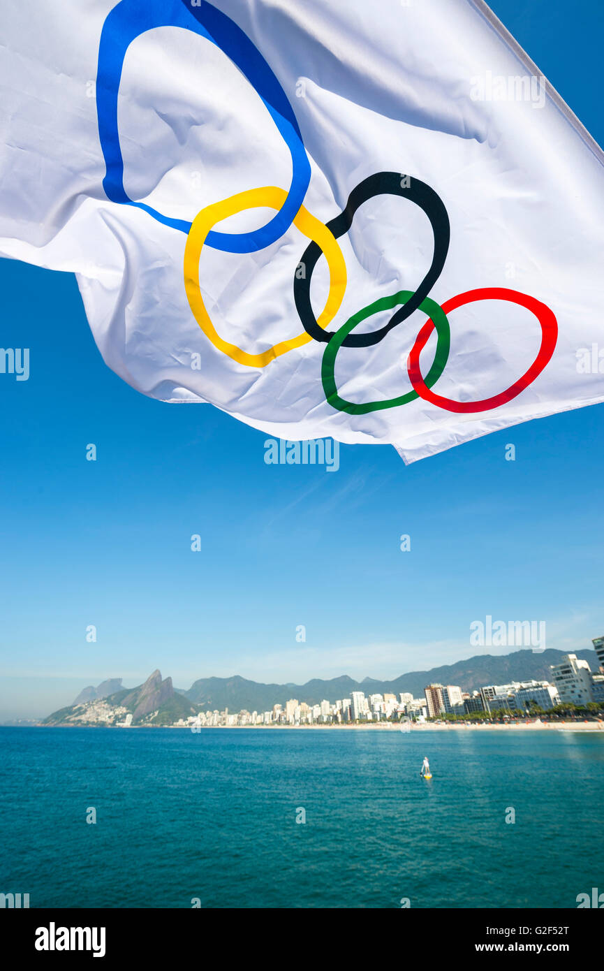 RIO DE JANEIRO - MARCH 27, 2016: An Olympic flag flutters in the wind above the city skyline at Ipanema Beach. - Stock Image