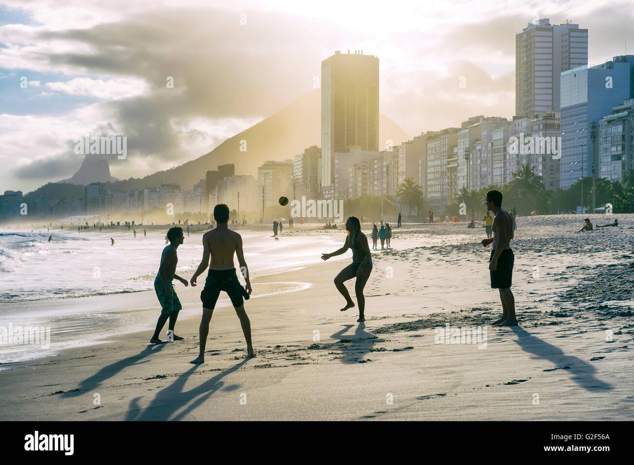 RIO DE JANEIRO - OCTOBER 30, 2015: Silhouettes of Brazilians play altinho beach football in a circle on Copacabana - Stock Image