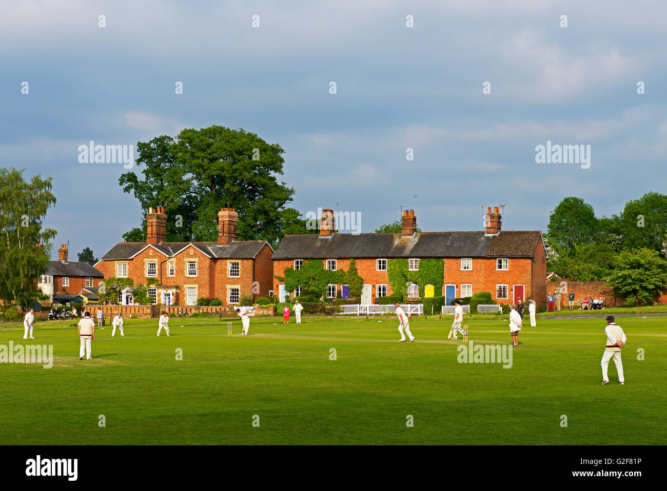 Game of cricket being played in the village of Hartley Wintney, Hampshire, England UK - Stock Image
