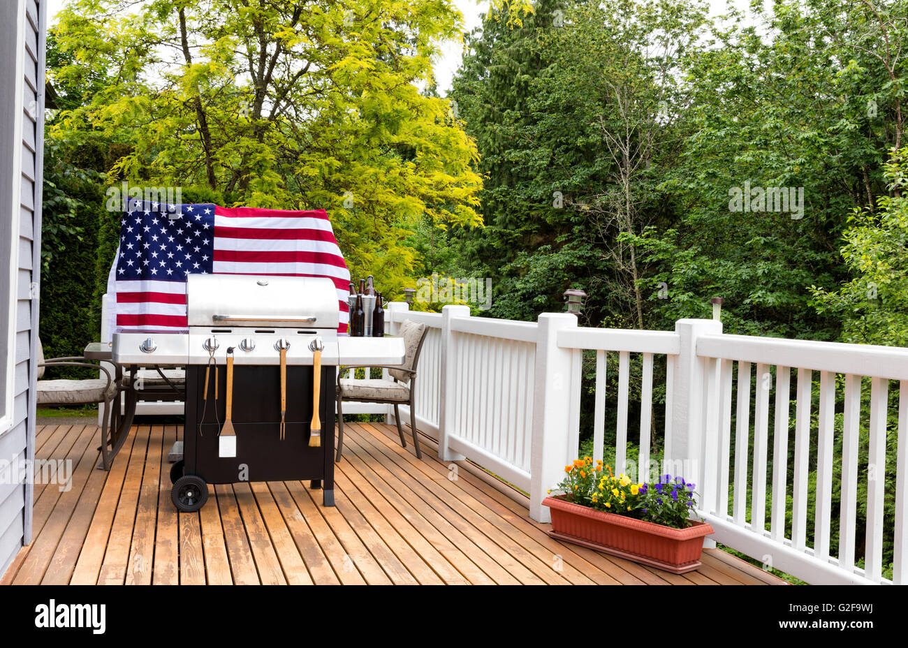 Home Outdoor Patio And Barbecue Cooker With Bucket Of Cold Bottled Beer On  Ice With USA Wooden Flag In Background.