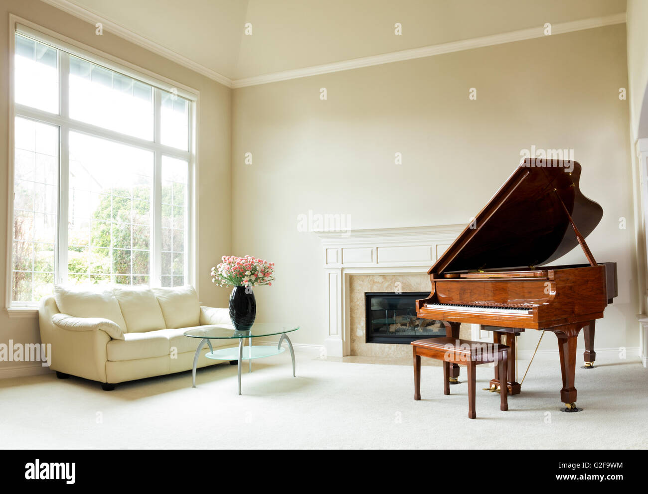 Living room with grand piano, fireplace, sofa and large window with ...