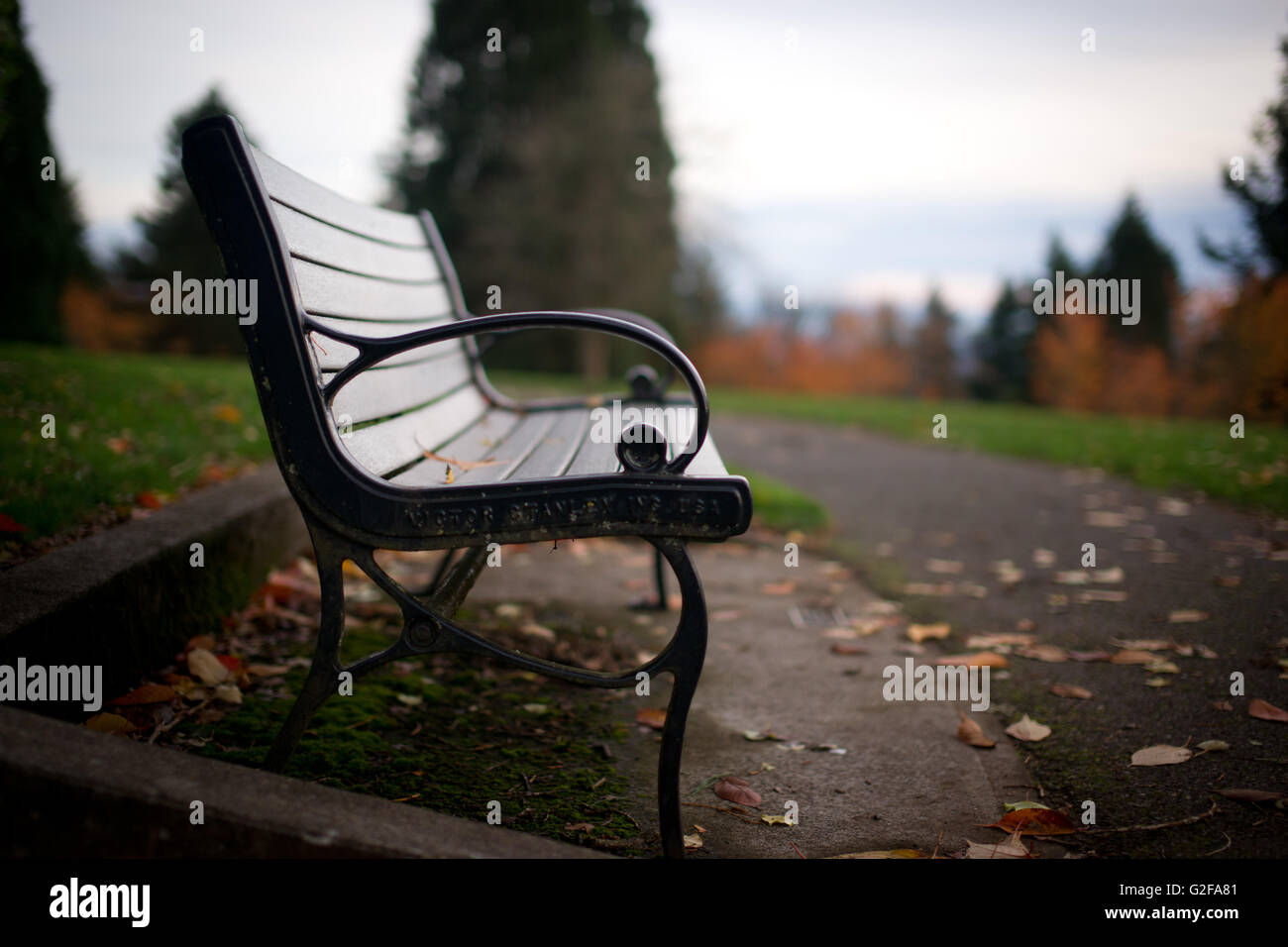 Park Bench Along Path - Stock Image
