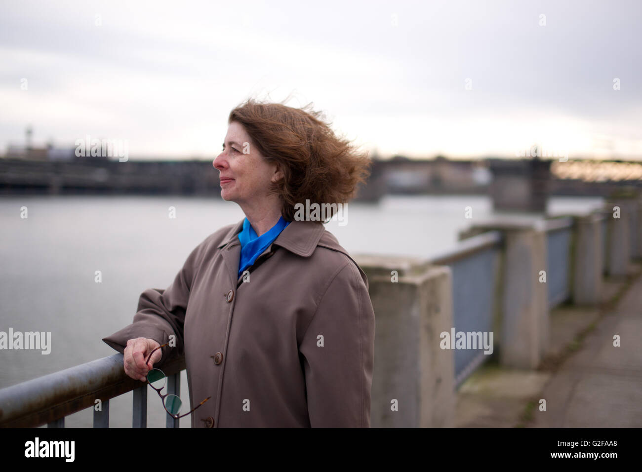 Mid-Adult Woman in Trench Coat Resting Arm on Railing While Looking Across River - Stock Image