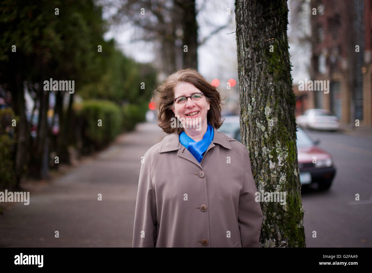 Smiling Mid-Adult Woman in Trench Coat - Stock Image