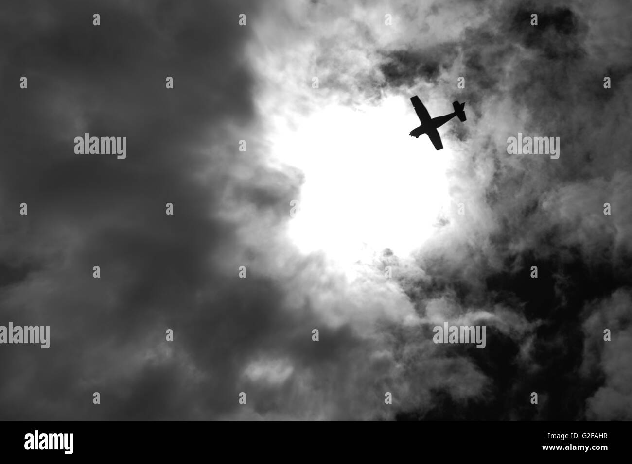 Airplane Silhouette Against Dramatic Sky, Low Angle View - Stock Image