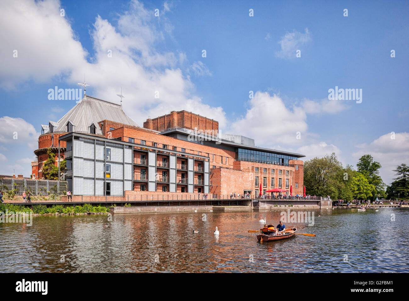 Royal Shakespeare Theatre and the River Avon and  people in boats on the river on a sunny weekend in late spring, - Stock Image