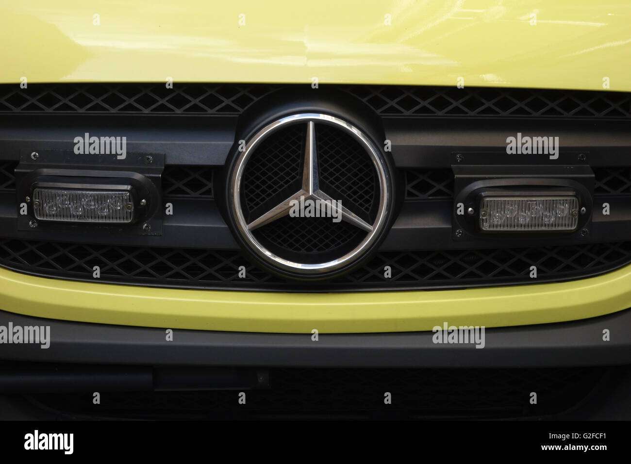 Front grille of a London Ambulance Service Mercedes Sprinter van showing the emergency lights - Stock Image