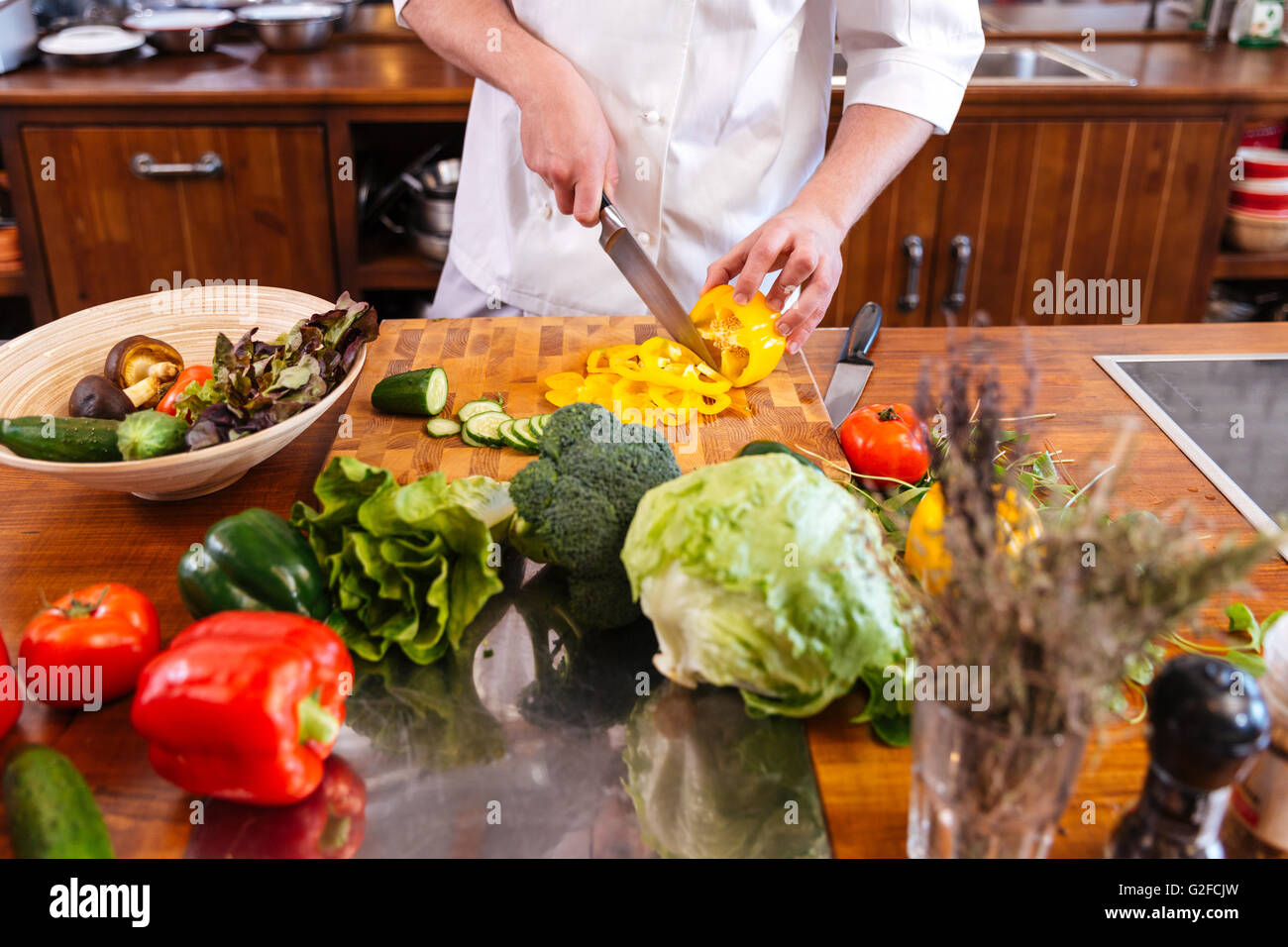 Closeup of chef cook standing and making salad on the kitchen - Stock Image