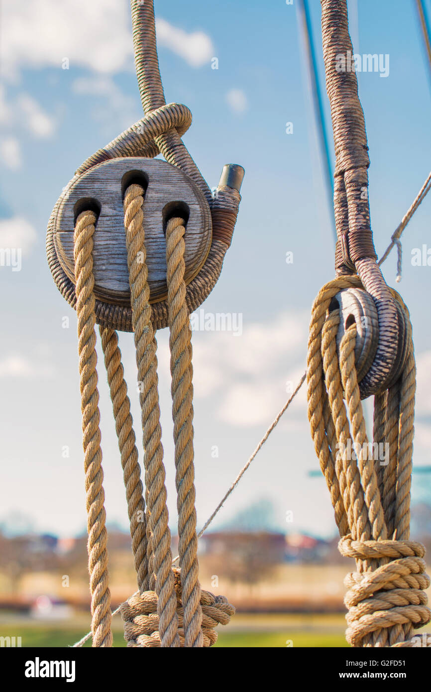 Vintage marine ropes and wooden tackle block on sailing vessel - Stock Image